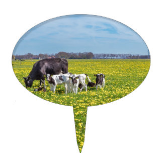 Cow with calves grazing in meadow with dandelions cake topper