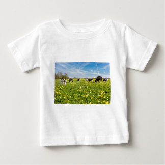 Cow with newborn calves in meadow with dandelions baby T-Shirt