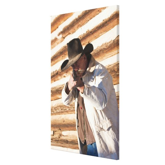 Cowboy aiming his gun, standing by an old log canvas print