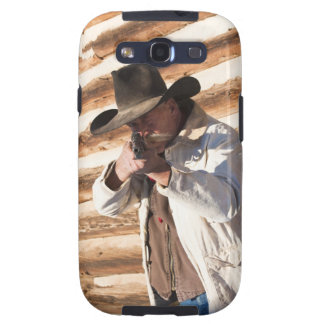 Cowboy aiming his gun, standing by an old log galaxy s3 cases