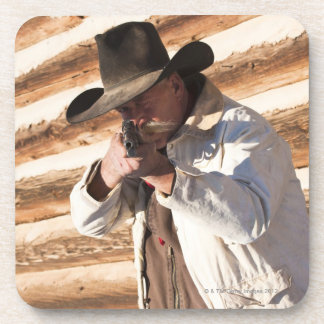 Cowboy aiming his gun, standing by an old log drink coaster