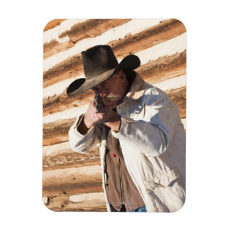 Cowboy aiming his gun, standing by an old log magnet