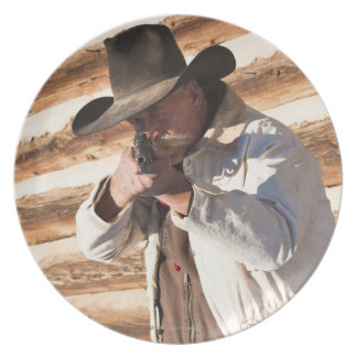Cowboy aiming his gun, standing by an old log dinner plate
