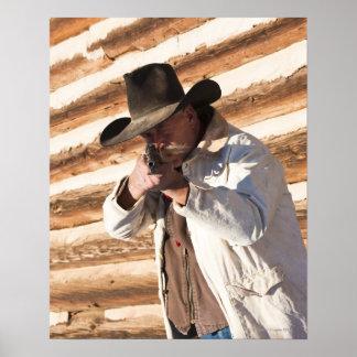 Cowboy aiming his gun, standing by an old log print