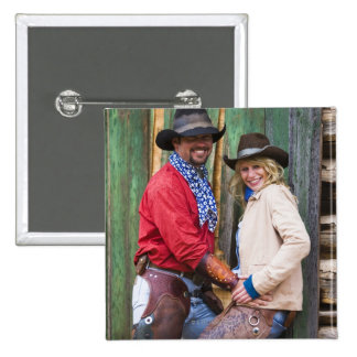 Cowboy and cowgirl holding hands in front of an 2 inch square button