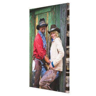 Cowboy and cowgirl holding hands in front of an canvas print