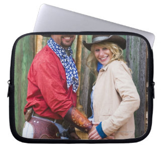 Cowboy and cowgirl holding hands in front of an computer sleeve