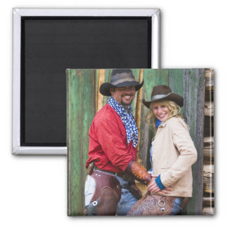 Cowboy and cowgirl holding hands in front of an magnet