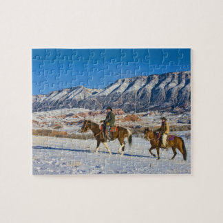 Cowboy and Cowgirl riding Horse through the Snow Jigsaw Puzzle