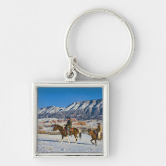 Cowboy and Cowgirl riding Horse through the Snow Keychain