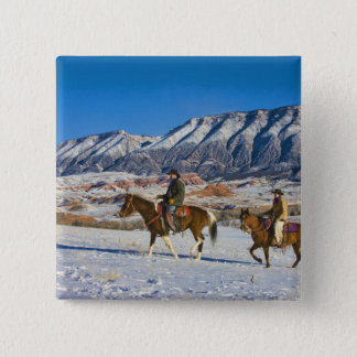 Cowboy and Cowgirl riding Horse through the Snow Pinback Button