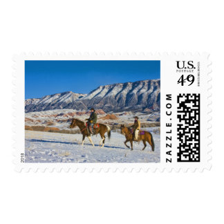 Cowboy and Cowgirl riding Horse through the Snow Postage