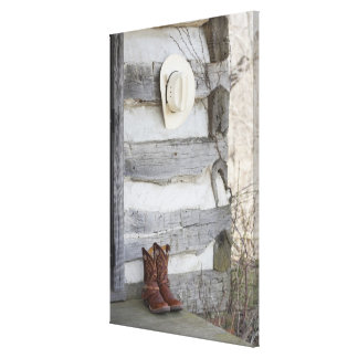 Cowboy boots and hat outside of log cabin canvas print