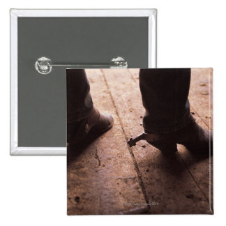 Cowboy boots with spurs on boardwalk at 2 inch square button