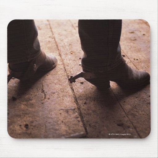 Cowboy boots with spurs on boardwalk at mousepad