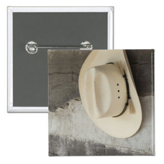 Cowboy hat hanging on wall of log cabin button