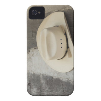 Cowboy hat hanging on wall of log cabin iPhone 4 cover