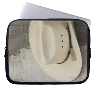 Cowboy hat hanging on wall of log cabin laptop computer sleeves