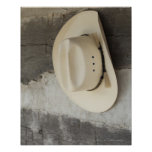Cowboy hat hanging on wall of log cabin poster