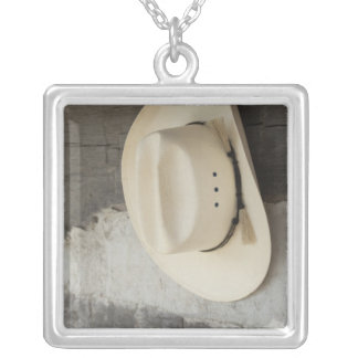 Cowboy hat hanging on wall of log cabin square pendant necklace