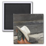Cowboy hat on cowboy boots outside a log cabin 2 inch square magnet