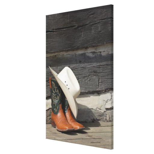 Cowboy hat on cowboy boots outside a log cabin canvas print