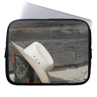 Cowboy hat on cowboy boots outside a log cabin computer sleeve