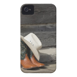 Cowboy hat on cowboy boots outside a log cabin iPhone 4 case