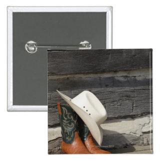 Cowboy hat on cowboy boots outside a log cabin pinback button