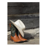 Cowboy hat on cowboy boots outside a log cabin postcard