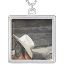 Cowboy hat on cowboy boots outside a log cabin silver plated necklace