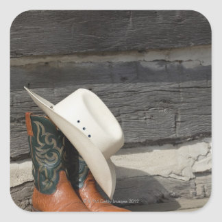 Cowboy hat on cowboy boots outside a log cabin sticker