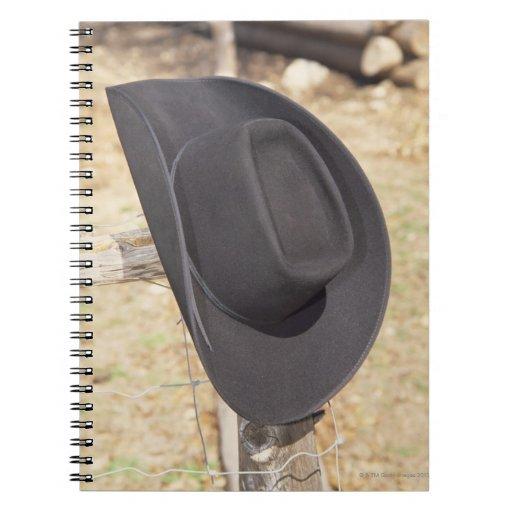 Cowboy hat on fence spiral notebook