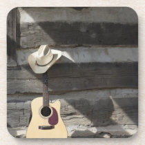 Cowboy hat on guitar leaning on log cabin coaster