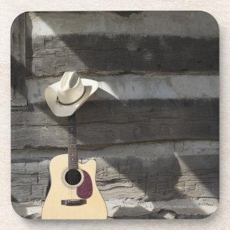 Cowboy hat on guitar leaning on log cabin beverage coasters