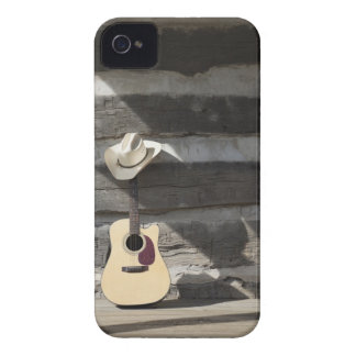 Cowboy hat on guitar leaning on log cabin iPhone 4 cover