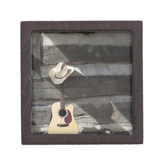 Cowboy hat on guitar leaning on log cabin jewelry box