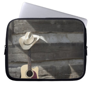 Cowboy hat on guitar leaning on log cabin laptop sleeves