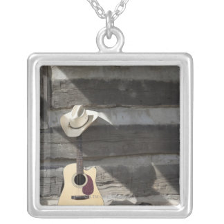 Cowboy hat on guitar leaning on log cabin necklaces