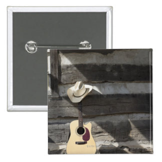 Cowboy hat on guitar leaning on log cabin pinback button