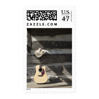 Cowboy hat on guitar leaning on log cabin postage