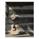 Cowboy hat on guitar leaning on log cabin poster