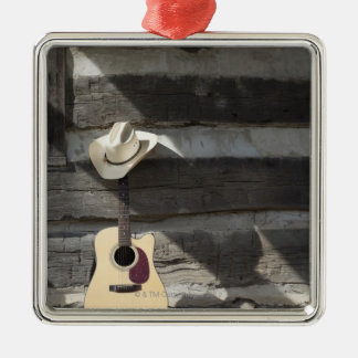 Cowboy hat on guitar leaning on log cabin square metal christmas ornament