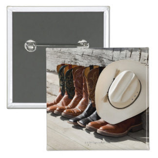 Cowboy hat on row of cowboy boots outside a log button