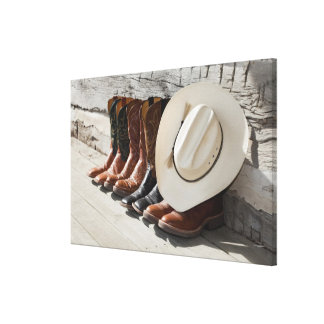Cowboy hat on row of cowboy boots outside a log canvas print
