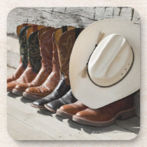Cowboy hat on row of cowboy boots outside a log coaster
