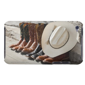 Cowboy hat on row of cowboy boots outside a log iPod touch covers