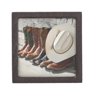 Cowboy hat on row of cowboy boots outside a log jewelry box