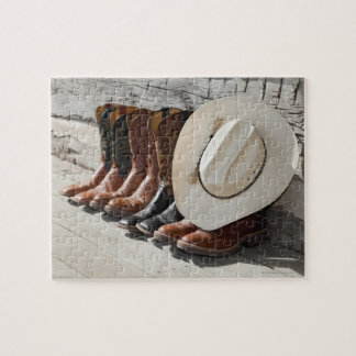 Cowboy hat on row of cowboy boots outside a log jigsaw puzzle