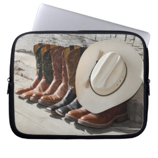 Cowboy hat on row of cowboy boots outside a log laptop computer sleeve